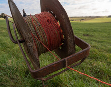 A Rusty Electric Fence Wire Reel With Green Countryside Background