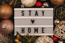 Stay Home Written On A Lightbox Among Christmas Decorations On A Dark Background. Christmas Time Pandemic Concept