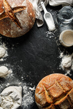 Background With Traditional Sourdough Loafs Of Bread And Ingredients For Making Them On A Black Background With Space For Text