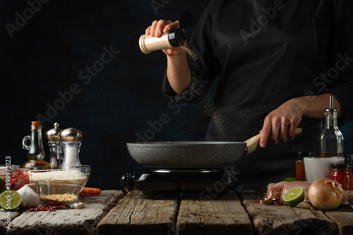 Professional chef pours spices into pan with frying chicken fillet Fototapete
