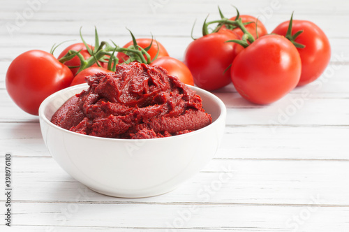 Obraz Traditional turkish tomato paste in bowl or spoon with fresh tomatoes on wooden table, homemade healthy food - fototapety do salonu