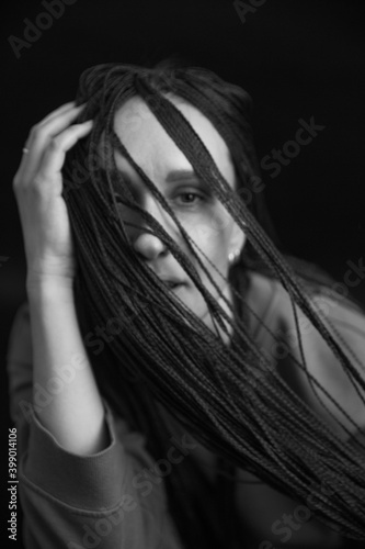 studio black and white portrait of a girl with African zizi braids, emotions on the face of a young woman, play of light and shadow in portrait photography