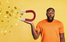 Surprised Black Man Holds A Big Magnet That Catches Money. Yellow Background