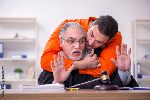 Canvas Print Old male judge meeting with young captive in courthouse