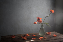 Red Poppies In Vase On Wooden Table