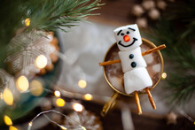 A Marshmallow Snowman Decorated With Icing. Gold Mug With Cocoa And Christmas Decor. Gingerbread In The Form Of Snowflakes.
