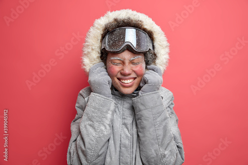 Photo of overjoyed woman wears hood of grey jacket smiles pleasantly has red face covered with frost goes skiing during December isolated over pink background Wallpaper Mural