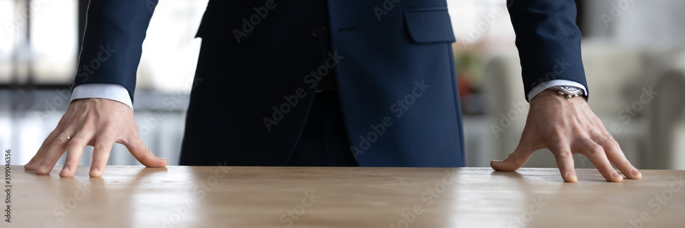 Fototapeta Horizontal banner close up confident businessman wearing suit standing at wooden office desk, employee executive boss putting hands on table, leadership and professional service concept