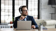 Dreamy businessman wearing headphones using laptop, sitting at desk in office, looking to aside, smiling employee executive dreaming, pondering future, listening to music after work done