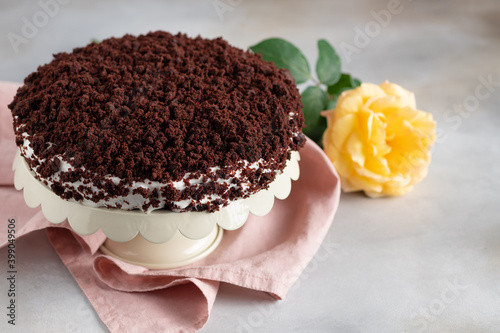 Leinwand Poster delicious chocolate cake with cream on gray background with yellow rose
