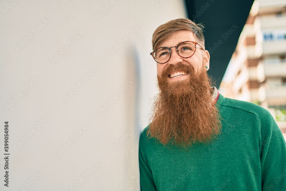 Fototapeta Young irish man with redhead beard smiling happy leaning on the wall at the city.