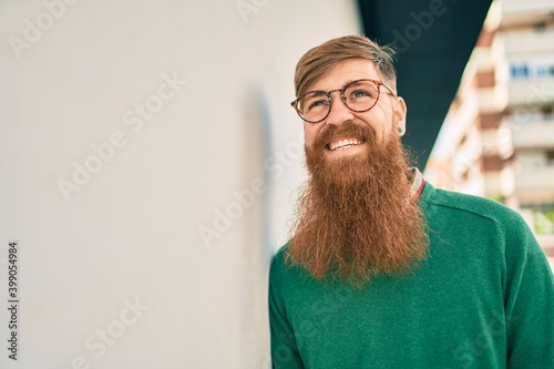 Obraz Young irish man with redhead beard smiling happy leaning on the wall at the city. - fototapety do salonu