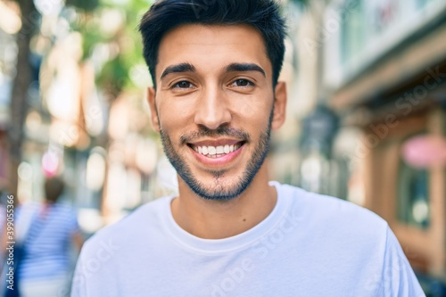 Obraz Young latin man smiling happy walking at the city. - fototapety do salonu