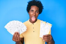 Handsome African American Man With Afro Hair Holding Boarding Pass And Bunch Of Dollars Sticking Tongue Out Happy With Funny Expression.