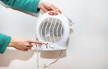 Heater Isolated On A White Background. A Girl Holds A Plastic Fan Heater And Shows The Temperature Controller.