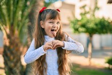 Adorable Caucasian Child Girl  Smiling Happy Doing Heart Symbol With Hands At The Park