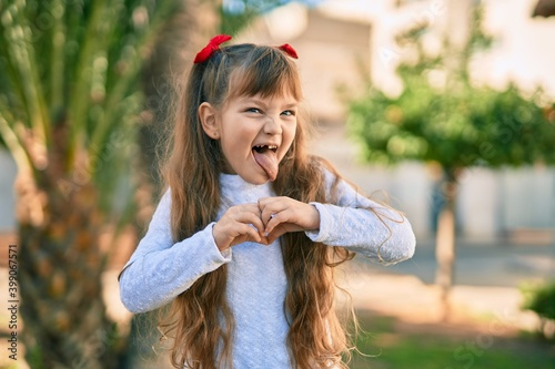 Adorable caucasian child girl  smiling happy doing heart symbol with hands at th Fototapeta