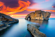 Sunset On The Coast. Fantastic Seascape And Giant Rocks At Fiery Sunset. Seascape And Island View Captured With Long Exposure Technique.