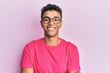 Young handsome african american man wearing glasses over pink background happy face smiling with crossed arms looking at the camera. positive person.