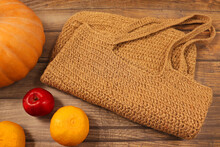 Close-up Photo Of Jute Yarn Shopping Bag, Mandarins, Apple And Part Of Pumpkin On Wood Background