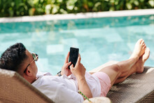 Man Spending Sunny Day By Swimming Pool And Using Mobile Application Or Checking Social Media On Smartphone