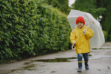 Rainy Day. Child Having Fun Outdoors. Kid With Umbrella.