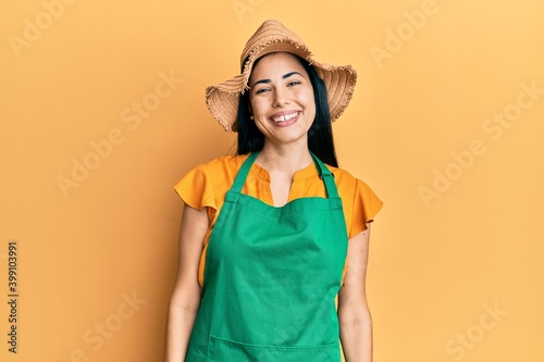 Fotografie, Obraz Beautiful young woman wearing gardener apron and straw hat with a happy and cool smile on face