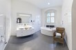 Leinwandbild Motiv Comfortable white bathtub and sink standing in modern bathroom with white walls and concrete floor. Interior with spectacular oval bath.