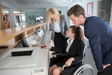 Female In Wheelchair Working In A Reception Of A Hotel