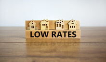 Low Rates Symbol. Wooden Blocks Form The Words 'loe Rates', Miniature House, Wooden Table. Beautiful White Background, Copy Space. Business And Low Rates Concept.