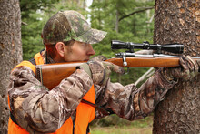 Adult Hunter Aiming Deer Rifle In Forest Close-up