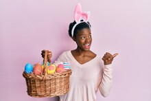 Young African American Girl Wearing Cute Easter Bunny Ears Holding Basket With Painted Eggs Pointing Thumb Up To The Side Smiling Happy With Open Mouth