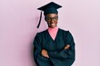 Young african american girl wearing graduation cap and ceremony robe happy face smiling with crossed arms looking at the camera. positive person.