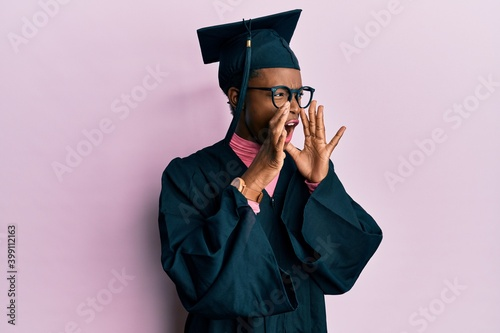 Obraz Young african american girl wearing graduation cap and ceremony robe shouting angry out loud with hands over mouth - fototapety do salonu