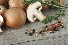 Fresh Champignon Mushrooms, Rosemary And Different Peppercorns On Wooden Table.