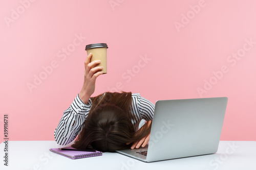 Fototapeta Sleepy bored woman office worker lying on table with laptop holding and showing paper coffee cup, feeling lack of energy sitting at workplace