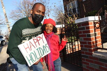 Man With Little Girl Outdoors Holding Happy Holidays Sign