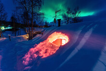 Mountain Cabin Fully Buried Under Snow, Night Photo With Green Aurora Lights Behind Heavy Winter Clouds. Northern Sweden, Lapland, Joesjo Village. Winter Season In Subpolar Area, Side View
