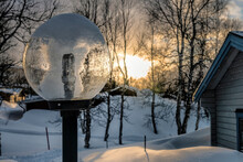 Close Up Photo On Round Garden Lamp Post Highlighted By Sunset In Scandinavian Mountain Village, Blurry Snowy Background With Birches, Part Of Wooden Cabin At Right Side