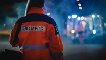 """Female EMS Paramedic Proudly Standing With Her Back Turned To Camera In High Visibility Medical Orange Uniform With """"Paramedic"""" Text Logo. Successful Emergency Medical Technician Or Doctor."""