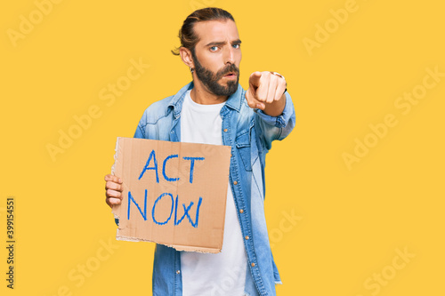 Attractive man with long hair and beard holding act now banner pointing with fin Wallpaper Mural