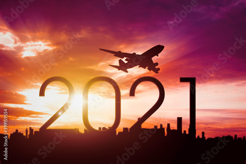Aircraft flying in sky above 2021 numbers and city