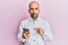 Young Hispanic Man Using Smartphone Making Fish Face With Mouth And Squinting Eyes, Crazy And Comical.