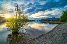 Sunset With Dramatic Clouds And Wooden Jetty At Derwentwater Lake In The Lake District, UK.