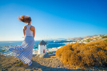 Female Tourist Looking At Mykonos Windmill On Windy Day