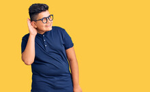 Little Boy Kid Wearing Casual Clothes And Glasses Smiling With Hand Over Ear Listening An Hearing To Rumor Or Gossip. Deafness Concept.