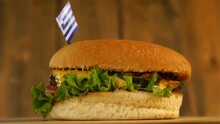 Delicious Burger With Small Greek Flag On Top Of Them With Toothpicks. Yummy Hamburger Rotating.