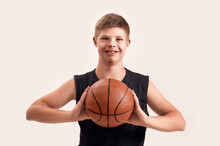 Cheerful Disabled Boy With Down Syndrome Smiling At Camera, Holding Basketball While Posing Isolated Over White Background