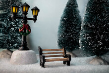 Miniature Winter Landscape With Snowy Trees, Wooden Bench And Street Lantern