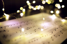Old Sheet With Christmas Music Notes As Background Against Blurred Lights. Christmas Music Concept